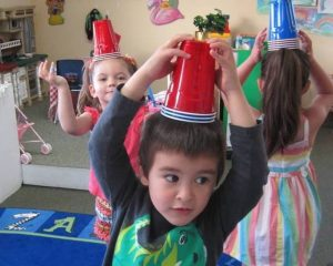 Children marching around a room with red and blue stackable cups on their heads.
