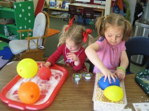 Two preschool girls in classroom at Discovery Trails Early Learning Academy rolling balloons into two trays of materials for a science experiment.