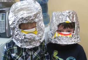 Two preschool boys at Discovery Trails Early Learning Academy wearing astronaut helmets made of paper and foil.