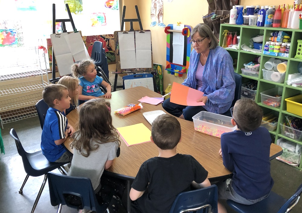 Peggy Priest, teacher at Discovery Trails Early Learning Academy giving art instructions at a learning table to five preschoolers.