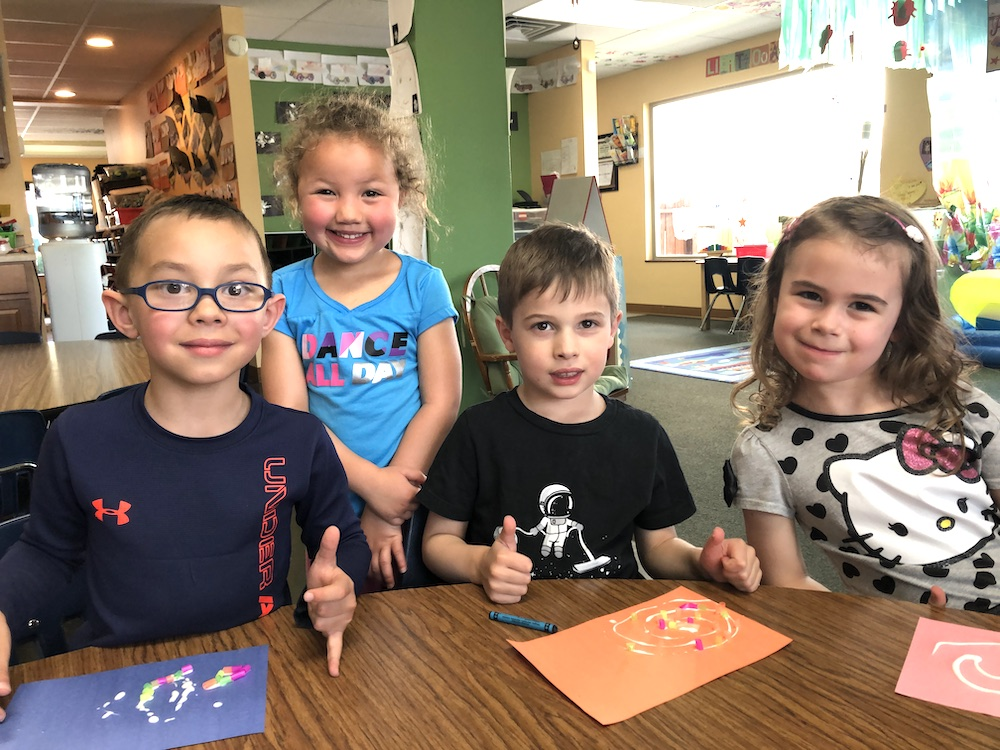 Four preschoolers attending Discovery Trails Early Learning Academy smiling for the camera at a school table.