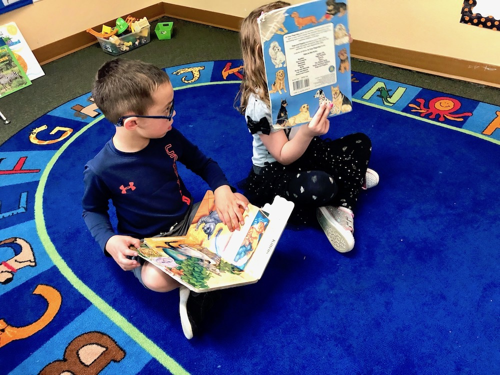 Preschooler boy and girl sitting on blue classroom carpet at Discovery Trails Early Learning Academy reading books.