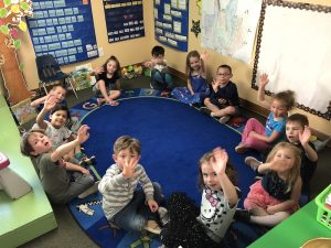 Students at Discovery Trails Early Learning Academy sitting in circle time on blue rug waving.