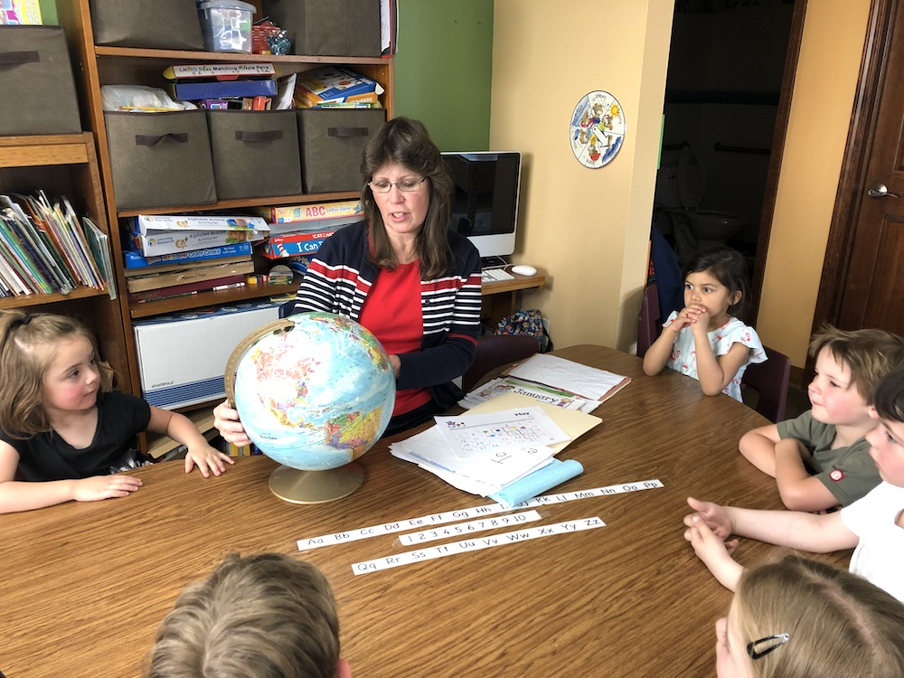 Lisa Draper, a teacher at Discovery Trails Early Learning Academy teaching a learning center about geography.