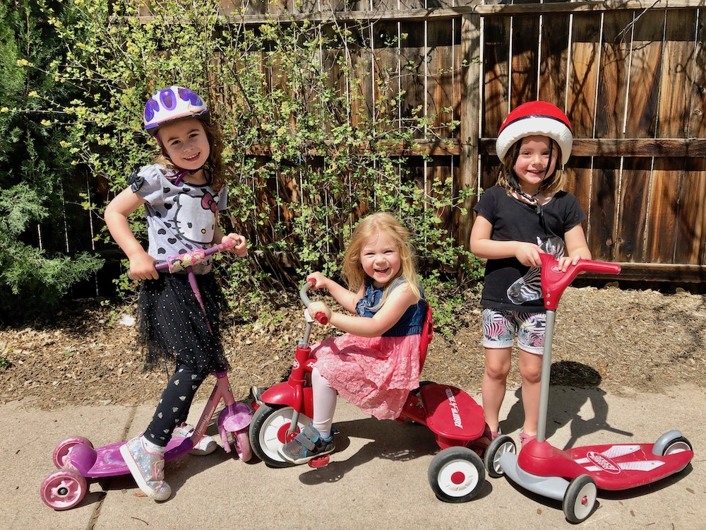 Three children playing outdoors on bikes and scooters at Discovery Trails Early Learning Academy.